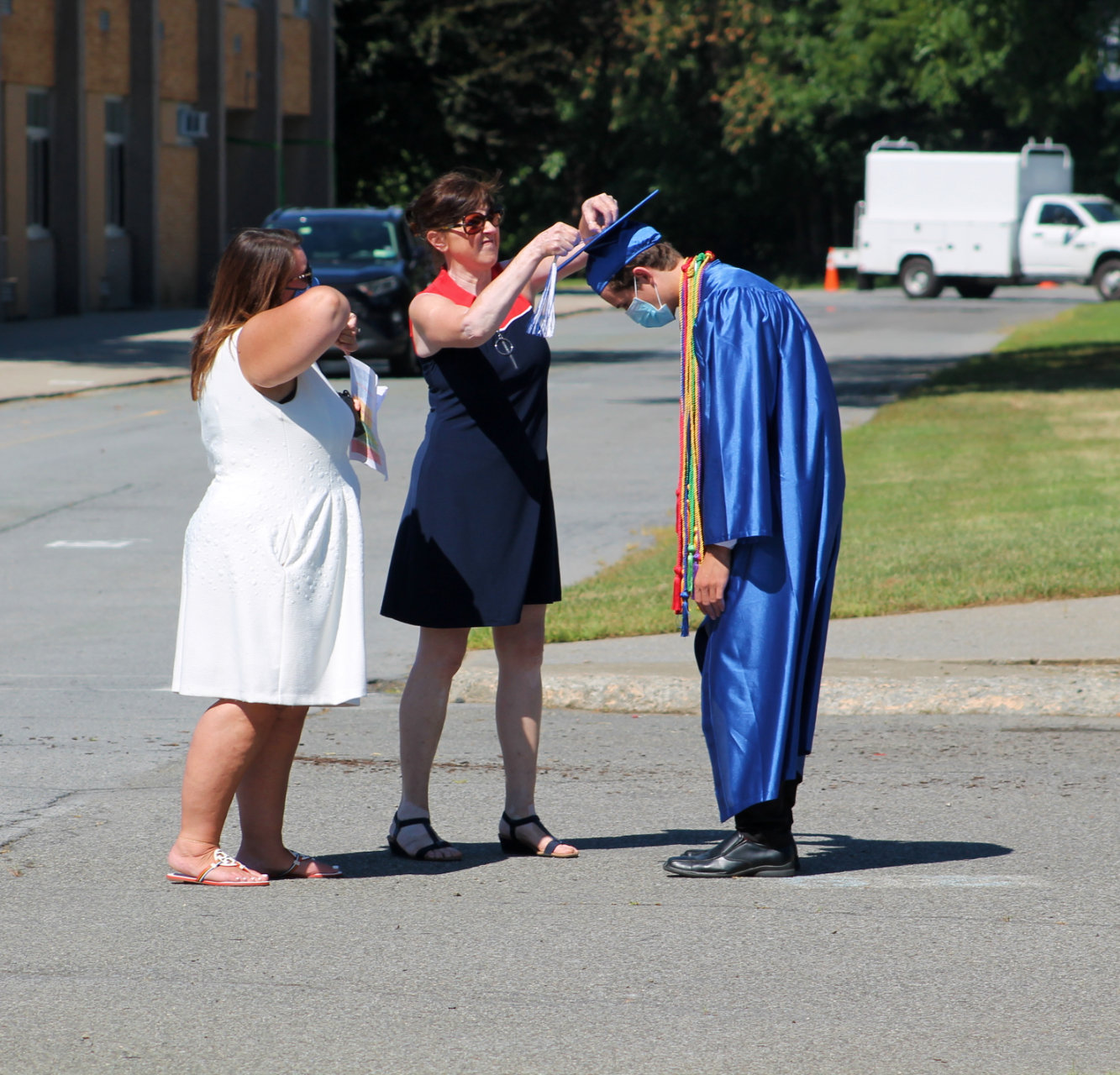 Senior Class Advisor, Antoinette Oakes and Graduation Coordinator, Kimberly Carver help Class of 2020 graduate Connor Fitzgibbons adjust his tassel.