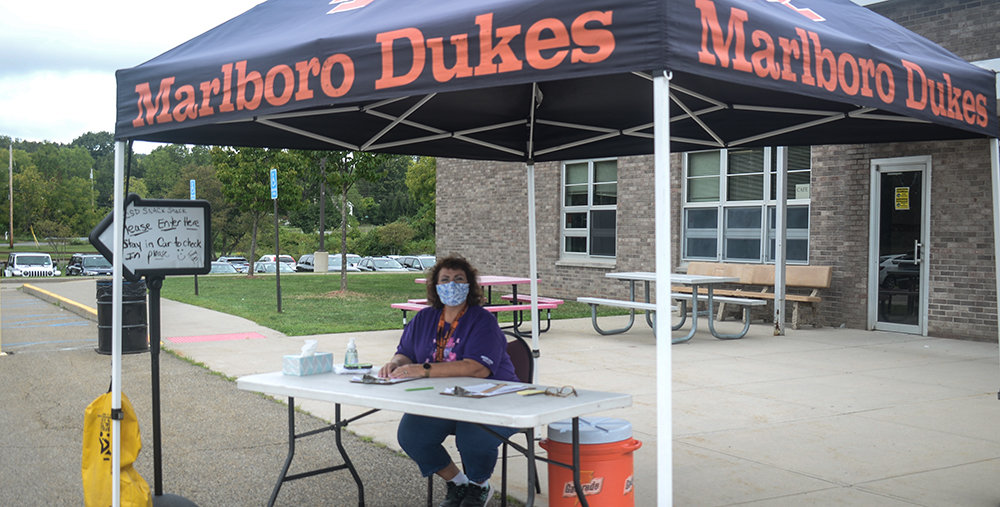 Food Services staff member Cindy J. sits at the Snack Shack welcome table where students provide their information before receiving their weekly supply of food.