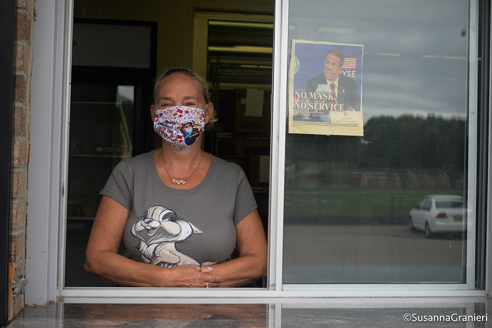 Cathy S., Food Services staff member, stands in the window where food is distributed to students and their families.