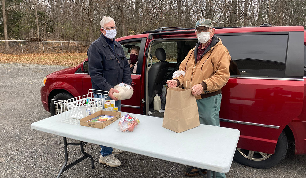 Town of Montgomery Food Pantry Treasurer Peter Sullivan (left) and volunteer Clifford Medley (right) give Bea Conn (center) a Thanksgiving meal.