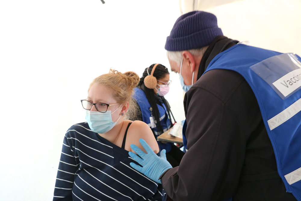 Randy Morse, a Registered Nurse with the Orange County Medical Reserve Corps, administers a vaccine to Elizabeth Black of the City of Newburgh, a preschool teacher.