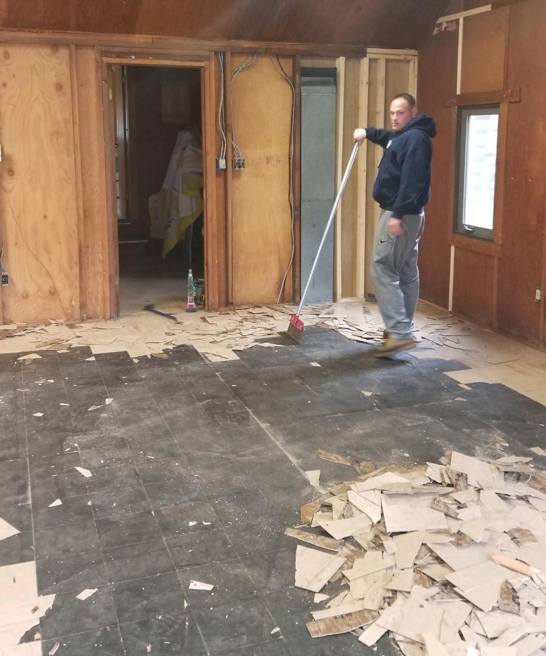 Anthony Romeo, program director for the Walden Recreation and Parks Department, redoes the floor of the main meeting room in the Walden Scout Cabin.