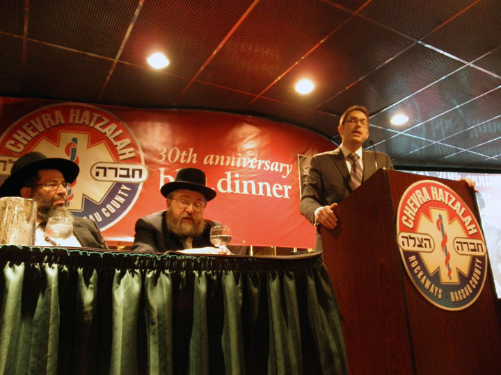 Hatzalah supporter Charlie Harary speaks alongside Rabbi Yaakov Bender and S. L. Wolkowitz.
