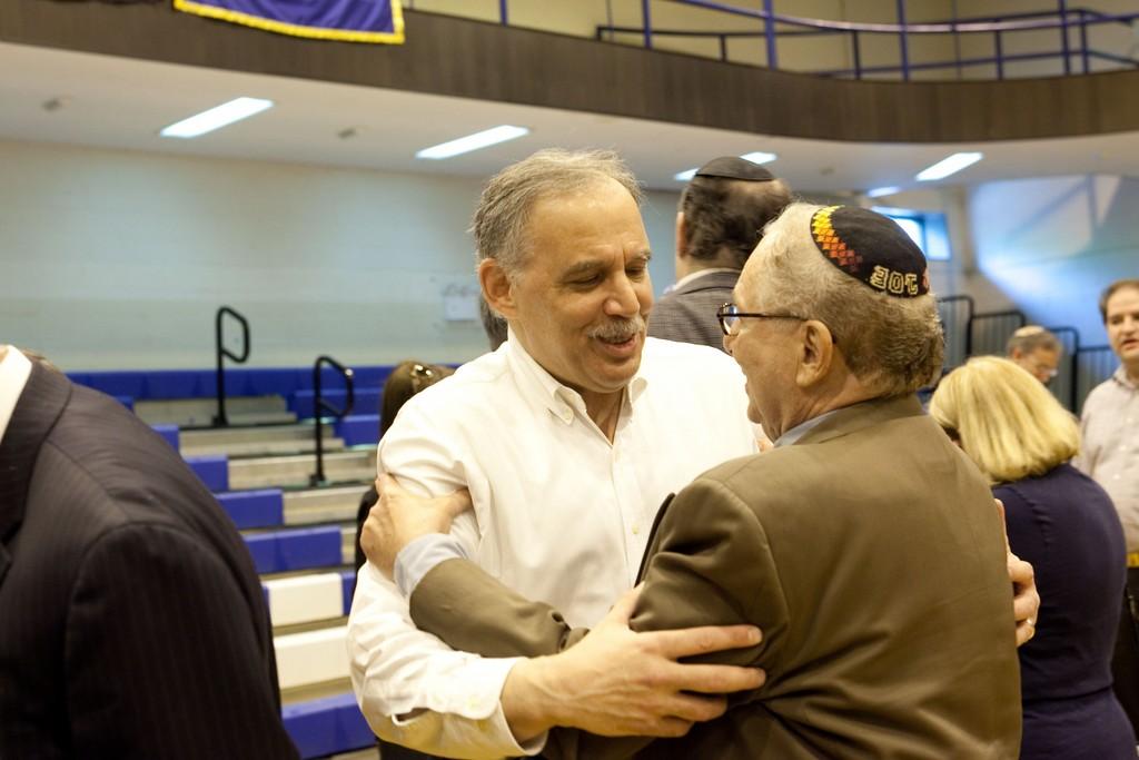 YU basketball alum Jerry Joszef greets Danny Halpert, coach's brother.