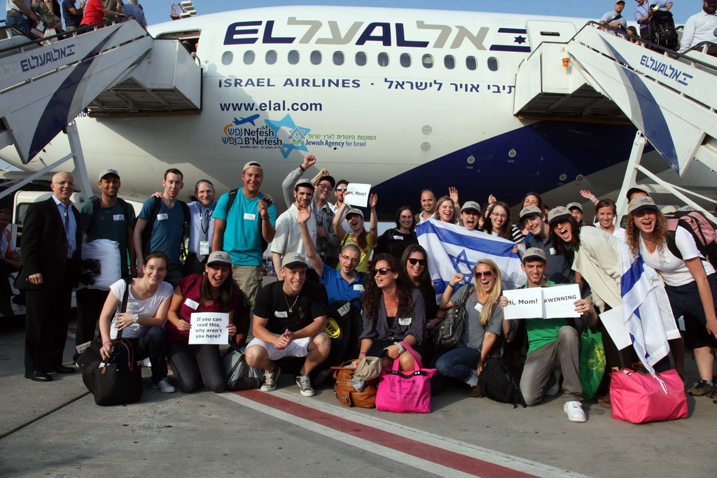 """A Nefesh B""""Nefesh charter Aliyah flight last summer with a large group of young professionals and singles. Founders Tony Gelbart (left) and Rabbi Yehoshua Fass (fourth from left) joined the group, organized with Israel's Ministry of Immigrant Absorption and the Jewish Agency for Israel."""