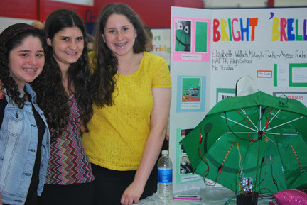 The Bright 'Brella would have LED light strips and pressure sensors inside the umbrella. When rain strikes the umbrella the light strips turn on for better vision in stormy weather. From left were HAFTR students Alyssa Fuchs, Mikayla Fuchs and Elizabeth Wallach.