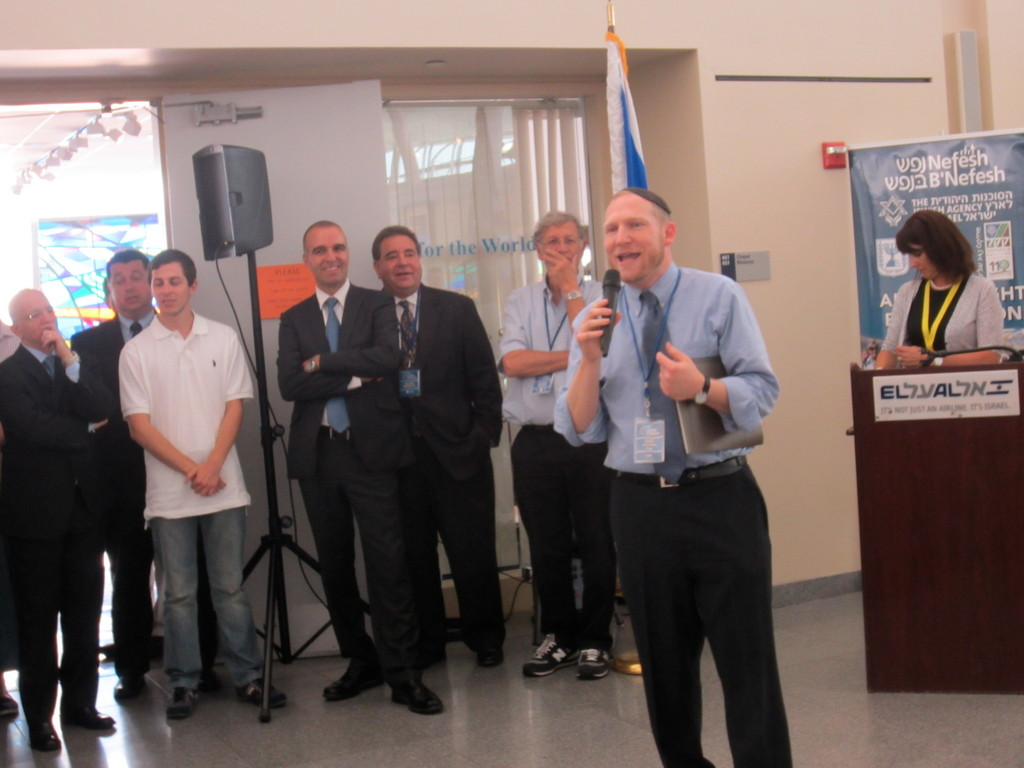 Rabbi Yehoshua Fass, NBN founder and executive director, speaks at JFK Airport last week before Nefesh B'Nefesh's latest flight of olim (immigrants), flanked by (from left) Erez Halfon, vice chairman of NBN; Russell Robinson, CEO of Jewish National Fund; and Shamai Keinan, Karen Kayemet L'Yisrael board member.