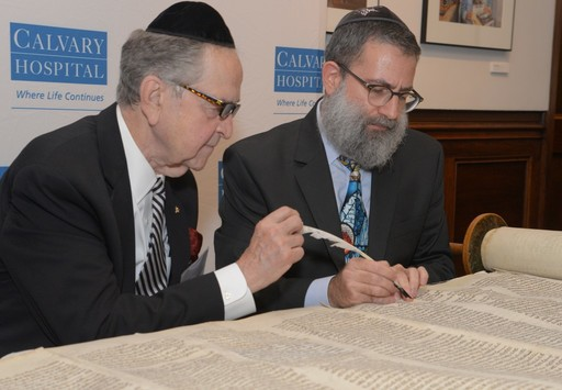 Rabbi Moshe Druin of Sofer On Site (right) guides Dr. Michael J. Brescia as he writes the first letter in the Torah restoration.