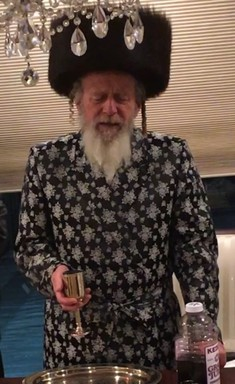 The Spinka Rebbe of Yerushalayim, Rabbi Avraham Yitzchok Kahana shlita, is pictured making havdalah in the Cedarhurst home of Avi and Sherry Ackerman, where he stayed recently while meeting with residents in the Five Towns.