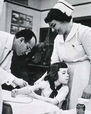 Jonas Salk gives the vaccine to a child as part of a field trial at a Pittsburgh elementary school.