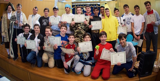 """North Shore Hebrew Academy Head of School Rabbi Jeffrey Kobrin (top left); Dr. Paul Brody of Great Neck (holding megillah container), and NSHA Middle School Principal Rabbi Adam Acobas. Student Danny Kroll (front row, third from left) """"hangs"""" a composite of modern day Hamans. Each year, Brody trains the students to read the Megillah Esther."""