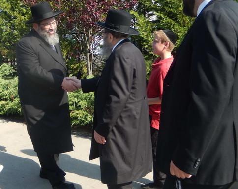 Rav Yaakov Bender greets Rav Kamenetsky.