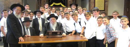 Rosh Hayeshiva Rabbi Mordechai Kamenetzky, founding Roth Yeshiva Rabbi Binyamin Kamenetzky, and the Novominsker Rebbe, surrounded by YOSS students.
