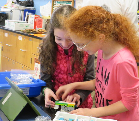 Two HANC students are learning to build a robot with Legos that has a sensor attached to it.