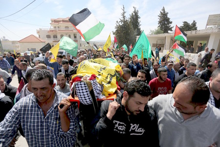 In March 2016 in the West Bank village of Deir Debwan, Palestinian mourners chant slogans while carrying the body of Mahmoud Shalan, who had tried to murder Israelis before security forces.