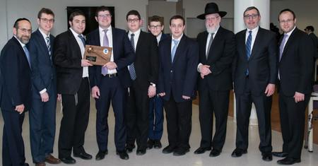 Lander College For Men Rabbi Yonason Sacks, Dean Moshe Sokol and Rabbi Aryeh Manheim congratulate the winning team.