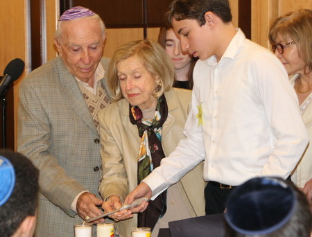 Manhattan Day School eighth grader Levi Langer accompanies survivors Garay and Lucy Lipiner in lighting candles in memory of their families who were murdered at the hands of the Nazis.