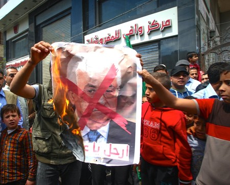 Palestinians burn a crossed poster depicting Palestinian President Mahmoud Abbas, in the southern Gaza Strip on April 14, 2017.