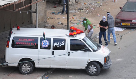 Palestinians throw rocks from behind an ambulance during a riot in Qalandiya.