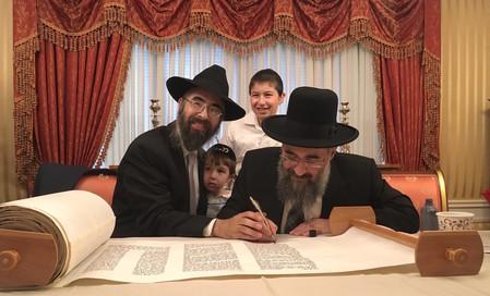 The new kehilla's rav, Rabbi Refael Ribacoff, his sons Avner Shmuel (left) and Moshe Ovadiya, and Rabbi Yitzchak Israeli completing the sefer Torah.