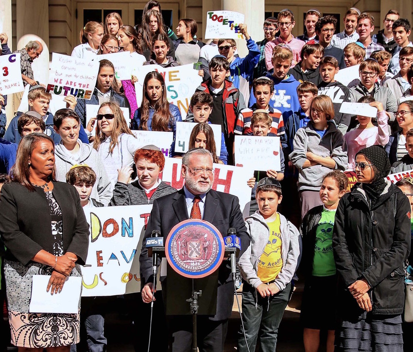 "Manhattan Day School students stand behind Orthodox Union Executive Vice President Allen Fagin during a City Hall rally. They asked Mayor deBlasio to include Jewish and Muslim students in the city's ""Free Lunch for All"" program, which does not yet offer kosher and halal options. City Councilwoman Leticia James, who spoke at the rally, is at left."