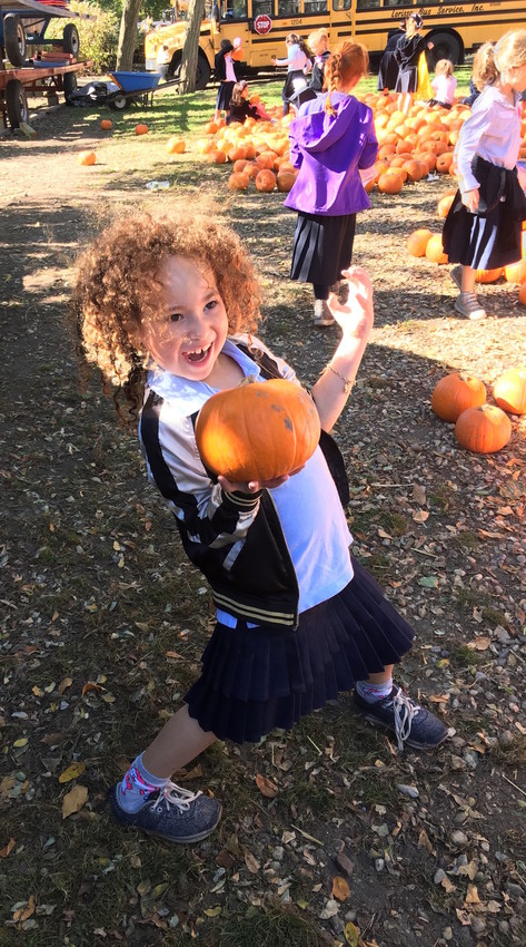 Esther Krohn, a first grader at the Shulamith School of Girls in Cedarhurst, shows off her freshly picked pumpkin.