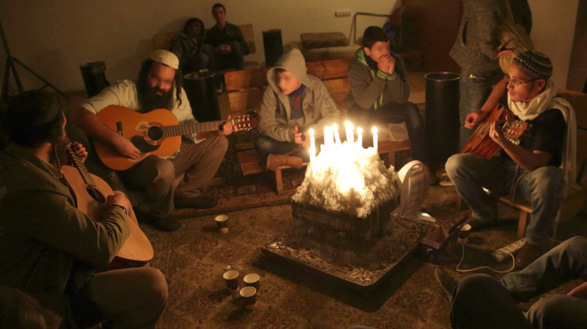 At night, the Zula Center is often packed with teens making music and clustered around a candle-filled table that serves as a sort of indoor bonfire. These teens' faces have been blurred to protect their identity.