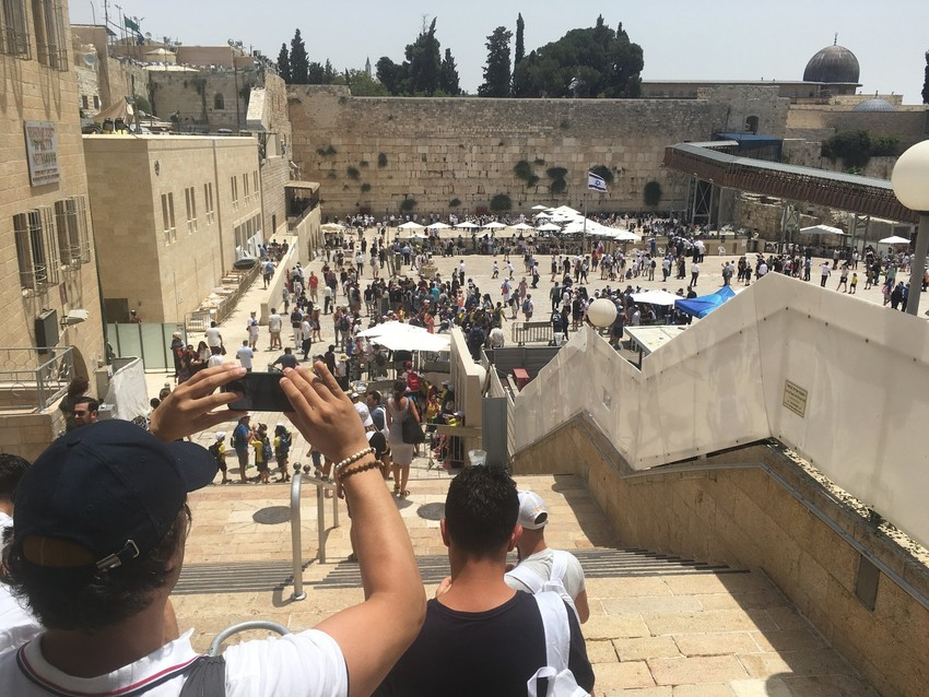 Tourists enter the Kotel plaza, as Jews pray at the holy site.