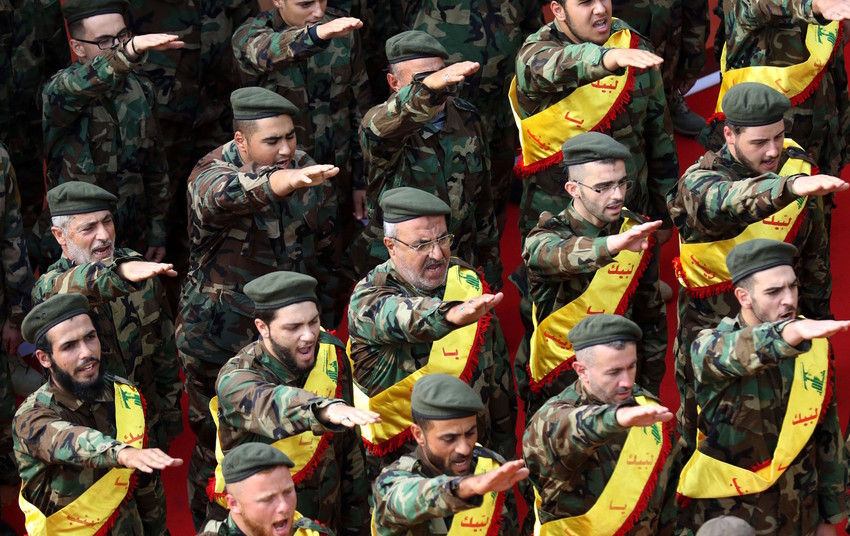 Members of Lebanon's Shiite Hezbollah movement salute behind the coffins of three comrades killed in combat in Syria during their funeral in the southern Lebanese city of Nabatieh on Nov 8, 2017.
