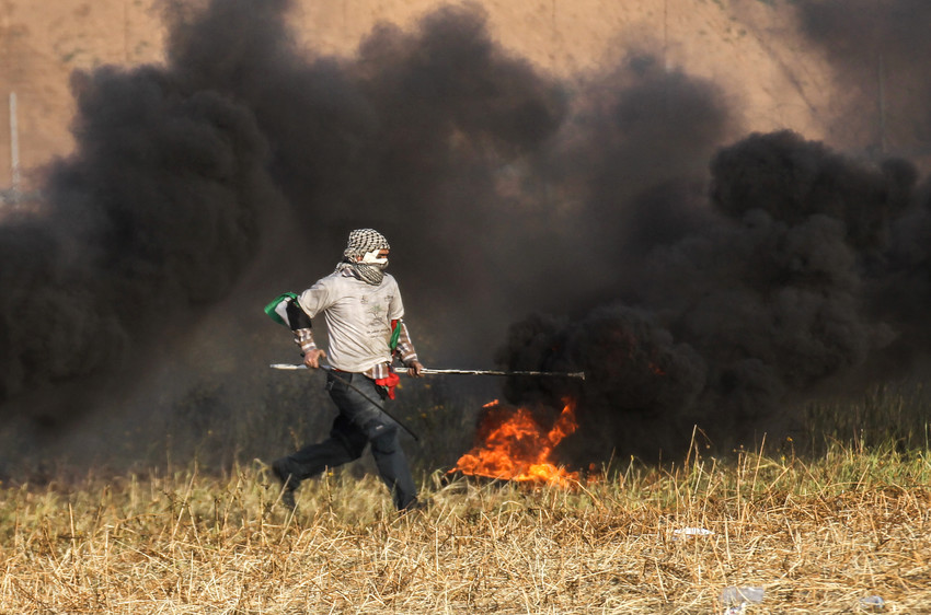 Palestinian protester burns tyres during clashes with Israeli forces near the border with Israel, east of Khan Yunis, in the southern Gaza Strip, on April 2.