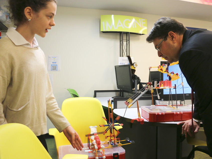 Tova Solomons demonstrates a Rube Goldberg machine for Minister Ofir Akunis.