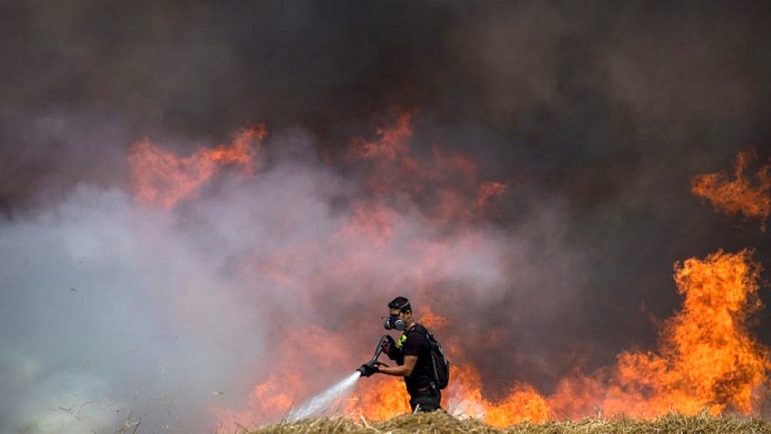 Israeli firefighters extinguish flames in a wheat field caused by kites flown by Palestinians near the Gaza border on May 30.