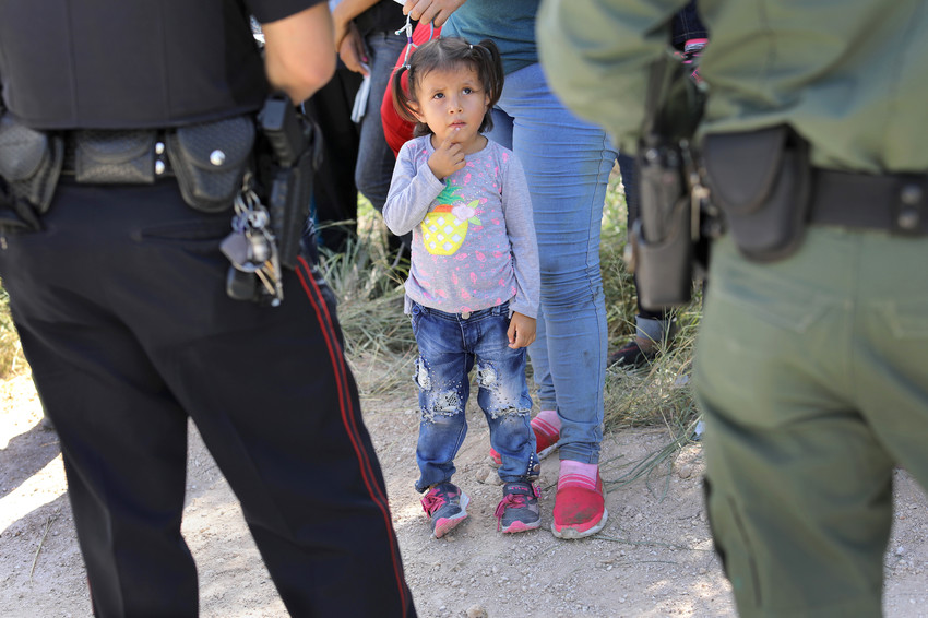 A child is accompanied by officers taking a group of Central American asylum seekers into custody near McAllen, Texas, on June 12.
