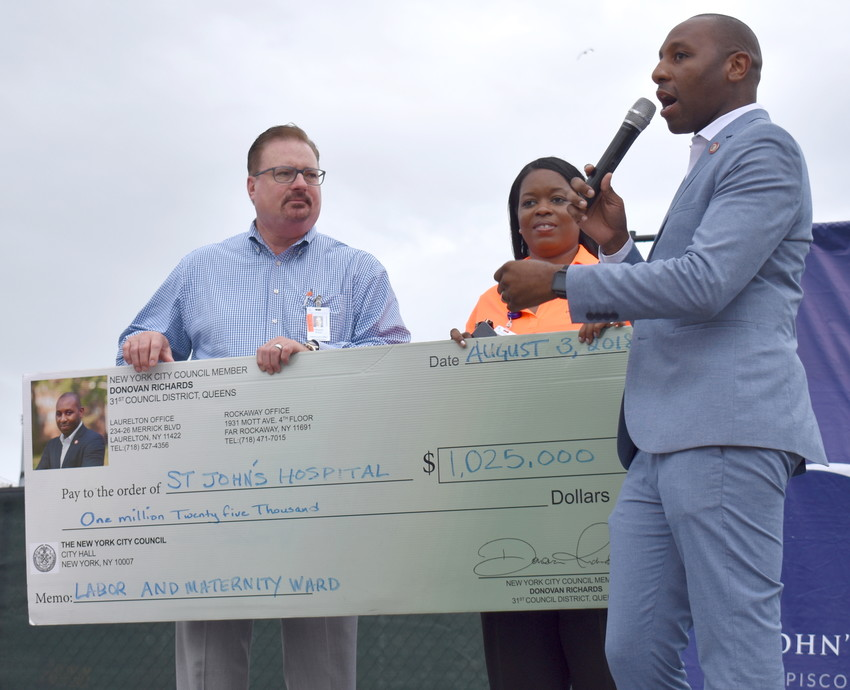 Hospital CEO Gerald Walsh and Vice President of External Affair Renee Hastick-Motes received a check for $1.025 million from Councilman Donovan Richards Jr. for renovation of the hospital's labor and delivery department.