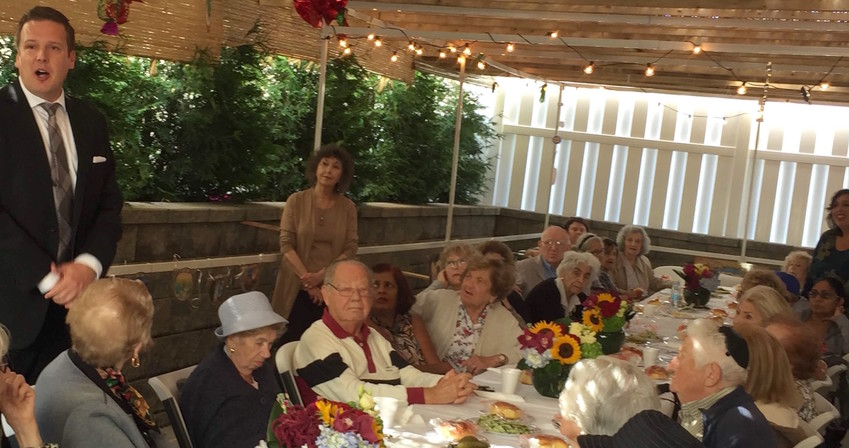 Five Towns Premier Rehabilitation Administrator Joseph Benden, in the Woodmere facility's sukkah with Shoah survivors.