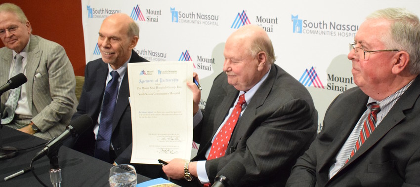 Joseph Fennessy, chairman of the board of South Nassau Communities Hospital, displays the ceremonial partnership agreement signed on Tuesday. Also pictured, from left: Mount Sinai President Dr. Arthur Klein, Mount Sinai CEO Dr. Kenneth Davis, and South Nassau President and CEO Richard Murphy.