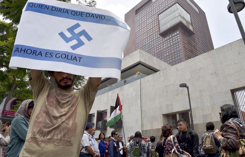 "A pro-Palestinian activist holds an Israeli flag painted with a Nazi swastika and the sentence ""Who would say that David … now is Goliath!"" during a rally against the Israeli military offensive in the Gaza strip outside the Mexican Foreign Ministry building in Mexico City on July 11, 2014."