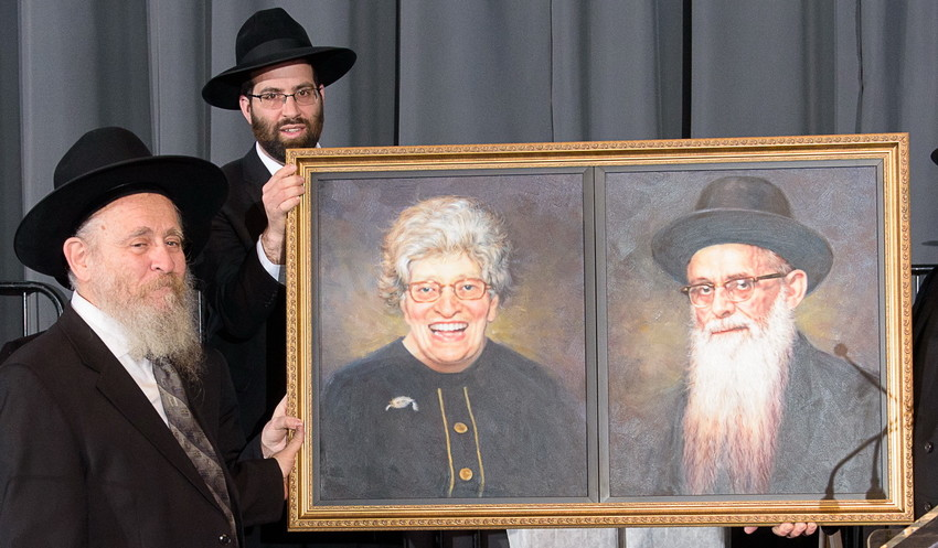 Rabbi Shmuel Feldman, Harbotzas Torah awardee, is presented with a portrait of his parents.