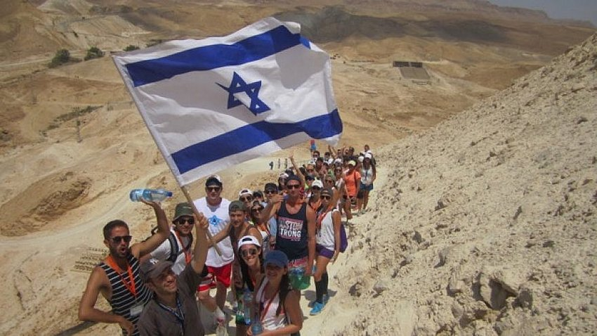 Birthright participants hike up Masada, Israeli flag in hand. 			           Birthright Israel.