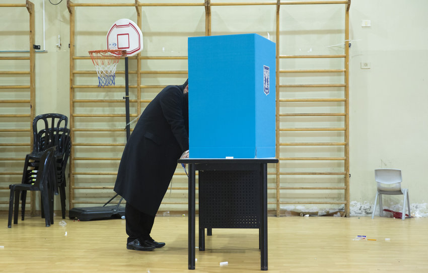 An haredi man stands behind a voting booth before casting his ballot in Israel's general elections on April 9 in Bnei Brak.