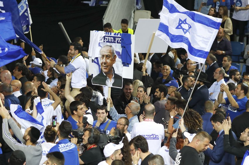 Supporters of the Israeli Likud Party wave party and national flags as they gather at its headquarters in the coastal city of Tel Aviv on election night,  April 10.