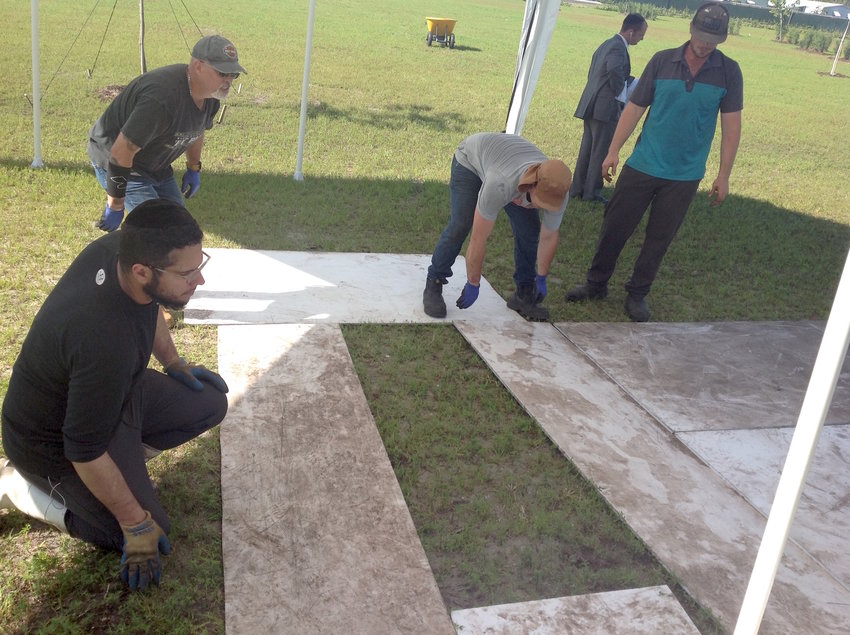 A team of Jewish men prepares a plot for burial at the South Florida Jewish Cemetery earlier this year.