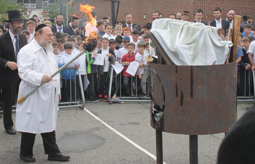 Rav Eliyahu Saldinger, second grade rebbi at Yeshiva Darchei  Torah, kindles the fire on the Far Rockaway campus, as Rav Dovid Morgenstern, menahel, looks on.