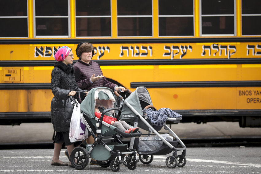Women pushing strollers walk past the Yeshiva Kehilath Yakov School in the South Williamsburg on April 9.
