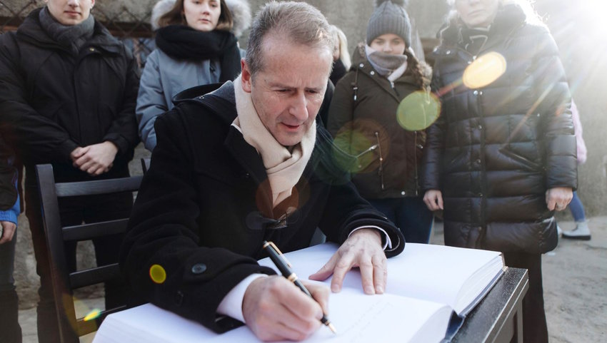 Volkswagen CEO Herbert Diess signs a guest book at Auschwitz, where the company runs an educational program for apprentices.
