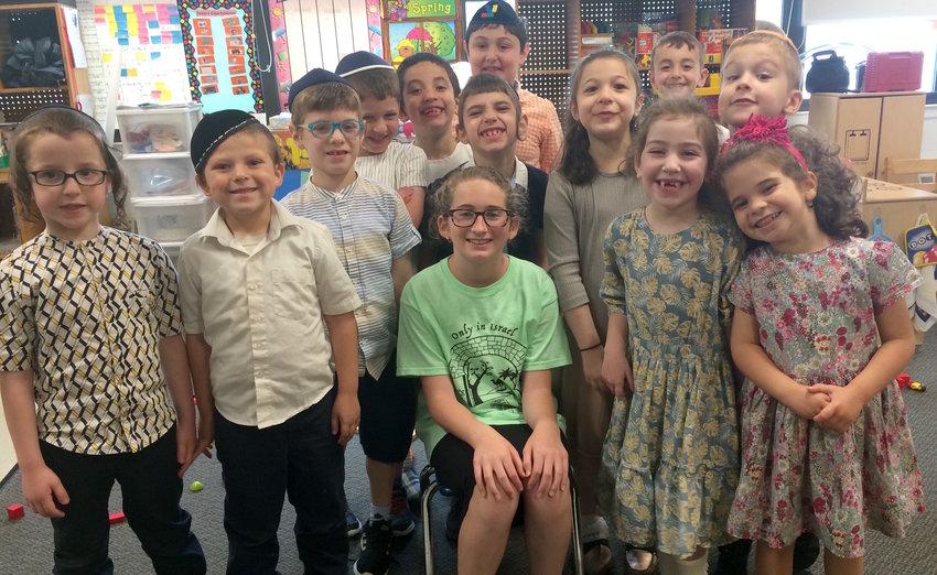 Adina, a sixth grader at HANC, is surrounded by CAHAL kindergarteners who graduated on June 18.