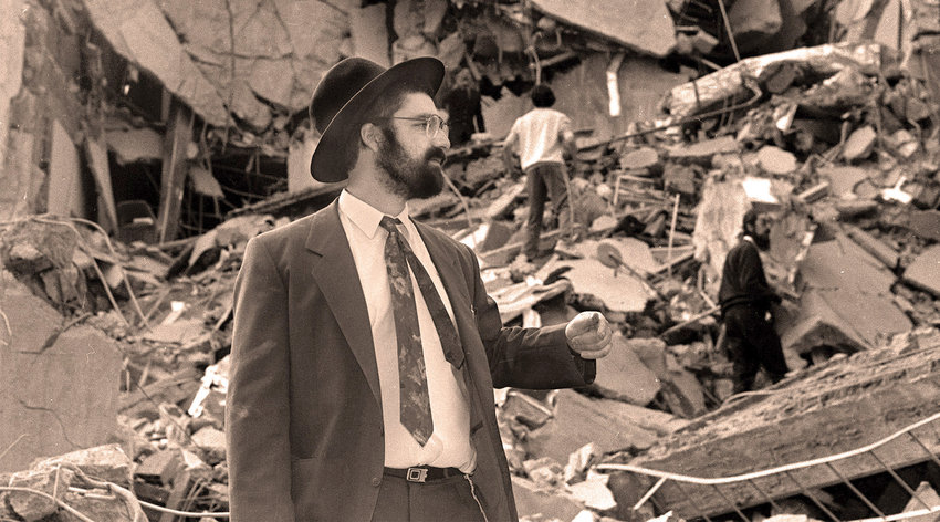 A man walks over the rubble after a bomb exploded at the AMIA Jewish center in Buenos Aires.