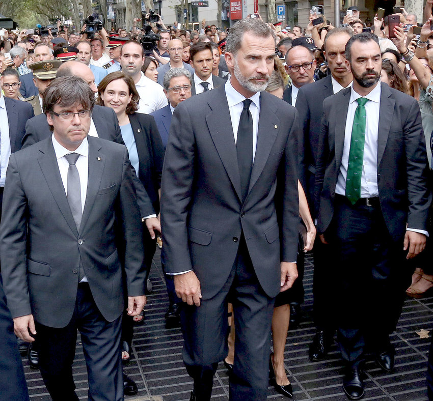 King Felipe VI of Spain (center), accompanied by Catalonia President Carles Puigdemont (left) and Barcelona Mayor Ada Colau, prepares to lay a wreath at the site of a truck-ramming attack two days earlier on La Rambla that left two people dead and more than 100 wounded.