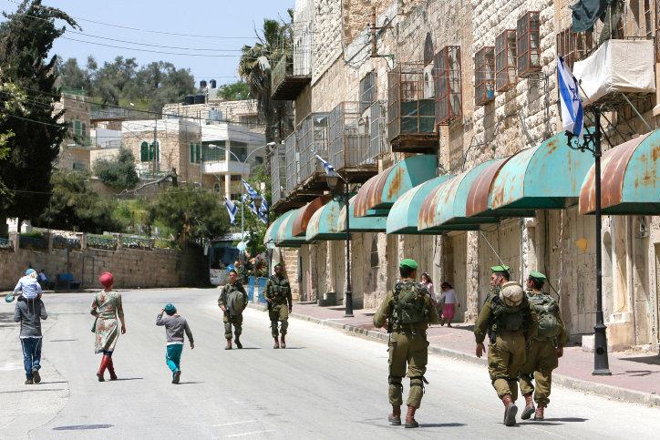 Israeli soldiers seen patrolling on Shuhada Street in Hebron, April 16, 2014.