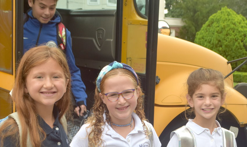HAFTR third-graders Michelle Hersh, 8, Juliet Weinrib, 7 and Grace Rosenberg, 8, are all smiles as they left their bus on the first day of school.